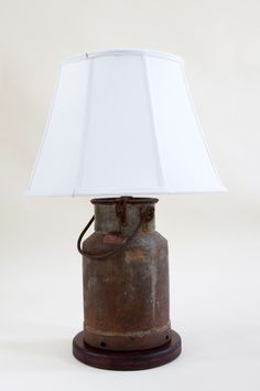 A rusty old Milk Pail is recreated into a classic table lamp, sitting on a stained timber base with a custom made fully lined linen lampshade.