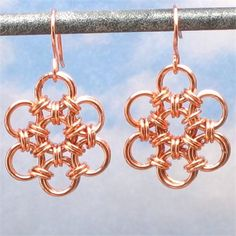 These very cute handmade chainmailearrings were made by winding solid copper wire into a coil and then sawing the coil into individual rings. I then wove the rings in a Japanese flower weave. Handcrafted copper ear wires were then added.   These earrings measure approximately 1-1/4 inches (3.2cm) from the top of the earwire to the bottom of the earring. They measure approximately  of an inch (2cm) wide.   These earrings are shiny copper, but they will age over time to a nice rich brown....