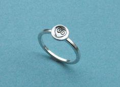 Ein schmaler Silberring mit quadratischem Querschnitt wird gekrönt  von einer kleinen Silberscheibe (6 mm) mit einem handgestempelten   Herz-Symbol.