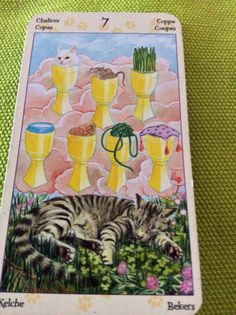 "7 of Chalices from the Tarot of the Pagan Cats deck by Lola Airaghi and Magdelina Messina. ""If you have built castles in the air, your work need not be lost; that is where they should be. Now put the foundations under them."" – Henry David Thoreau #Tarot #TarotSingapore #Quote"