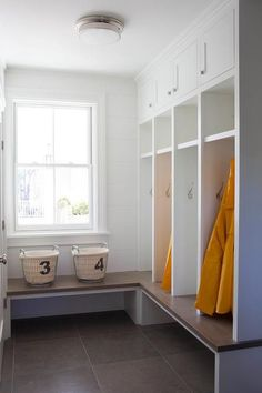 l-shaped mudroom fitted with white shiplap walls and a wood top bench positioned beneath a window and continuing around to an adjacent wall fitted with white built-in open lockers fixed beneath white overhead cabinets accented with polished nickel knobs. Mudroom Cubbies, Mudroom Cabinets, Mudroom Laundry Room, Bench Mudroom, Entry Bench, Vestibule, Built In Lockers, Garage Lockers, New Swedish Design