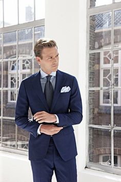 A deep blue suit and a light blue classic shirt will showcase your sartorial self. Shop this look on Lookastic: https://lookastic.com/men/looks/navy-suit-light-blue-dress-shirt-black-tie/21388 — Light Blue Dress Shirt — Black Tie — Light Blue Pocket Square — Navy Suit