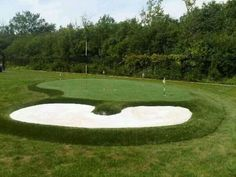 Backyard putting green with sand bunker installed by Krevitz Golf Turf Solutions.