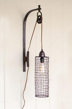 """Illuminate your space with this unexpected lighting focal piece. With a working pulley system and rustic finished metal, this wall sconce comes alive with industrial charm.15"""" x 5"""" x 26""""t"""