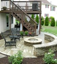 Paver patio under deck and side patio with stone veneer firepit and sitting wall...