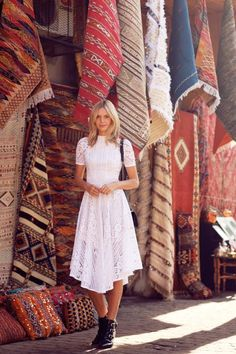 What to Wear With a Little White Dress - Blogger Jessica Stein of Tuula Vintage in a midi length white lace dress + booties, standing in front of gorgeous eclectic rugs