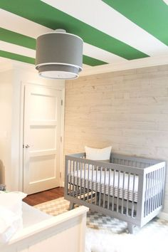 Bold colors and patterns on this green and white striped ceiling stimulate infant's sight | 5 reasons to decorate nursery ceiling.