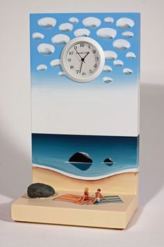 Time at the Beach by Pascale Judet. This clock is hand painted with acrylic on MDF, a wood product. The figures are HO scale figures made by Preiser. The clock is signed by the artist on the back. Battery operated.