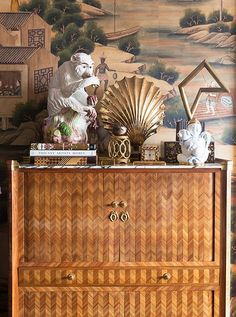 An inlaid-wood secretary, found in a New Orleans auction, shows off a curated vignette in radiant, golden hues.