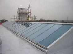 This 35m dual pitch rooflight to provide optimum natural light in a new school development. Panels are 2.8m span and have a blue tint to reduce solar gain and Activ self-cleaning glass to minimise maintenance. Opening lights are controlled by electrical actuators linked to a control panel with rain and thermostic sensors.