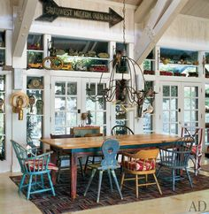 An extensive folk-art collection is displayed in the 4,500-square-foot house that actor Malcolm McDowell built with his wife, Kelley, north of Los Angeles. Chairs acquired during the family's travels wrap around the dining table, and friction toys are displayed above the french doors, which lead to the pool. (December 2009)