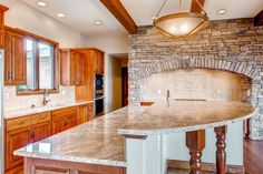 L-Shaped kitchen Large multi-level island Faux wood beams