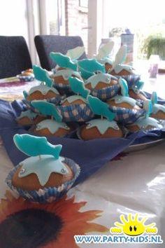 Dolfijnen cakejes. Nodig: Muffinmix + ingr., Snoep dolfijnen, lichtbl. fondant, Glazuur, Eetbare parels, cocktailprikker, cake vormpjes, Koekvormpje ster, poedersuiker.  Werkwijze: Bereid en bak de muffins/cupcakes volgens de verpakking en laat ze afkoelen. bestrooi de ondergrond met poedersuiker en rol het fondant uit, Steek hier sterretjes uit. Plak het fondant met glazuur vast op de cakejes. Druk in ieder puntje een pareltje. Prik een dolfijntje op een prikker en prik deze in het cakeje.