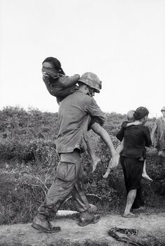A U.S. Marine carries a blindfolded woman suspected of Vietcong activities over his shoulder. She and other prisoners were rounded up during the joint Vietnamese-U.S. Operation Mallard, near Da Nang, Vietnam.
