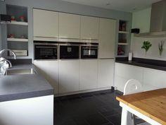 glanzende keuken met apart spoel-/ en kookgedeelte en kastenwand ...