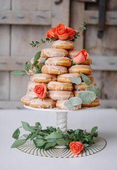 Las tartas con donuts se pueden adaptar fácilmente al estilo de tu boda. Unas rosas y ramas de eucaliptos transforman esta dulzura en un pastel vintage.