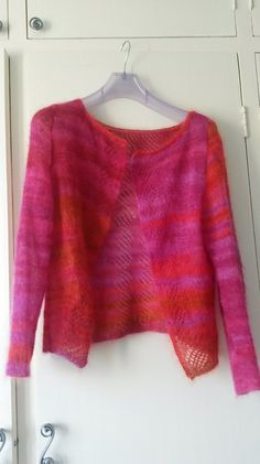 Cables, lace and garter stitch combine together to make an open backed cardigan that closes at the neck.