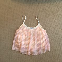 Cute cropped tank top Cropped and has a pink and cream chevron print. Super cute with high waisted jean shorts. Very flowy material so it's very comfortable. PacSun Tops Tank Tops