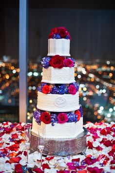 Gorgeous wedding cake with red and purple flowers. Photography by Adam Nyholt, Photographer.