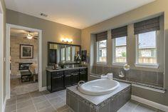 Gehan Homes Master Bathroom - Fireplace, black cabinets, luxury spa bathtub, brushed nickel hardware, gray tile. Houston, Texas   Harper's Preserve - Villanova #Gehanhomes