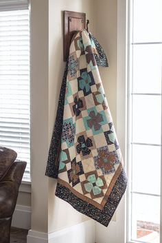 Fabrics printed with letters and numbers reminded designer Lacey Schipnewski of the teacher's manual she and her mom used to play with – it was called On Cherry Street. The quilt block is fun to make, and the subtle blue, brown, and black color scheme makes it a pleasing quilt.