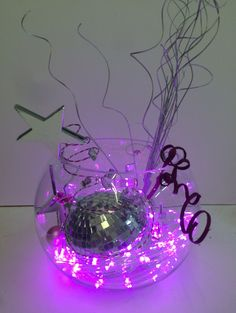 Dance to the disco along with this cool light up centerpiece! Just throw some string lights and a disco ball together and get the party groovin! http://www.flashingblinkylights.com/light-up-products/light-up-decorations/led-string-lights.html
