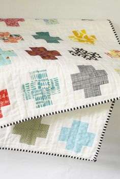 Modern log cabin cross quilt. black and white striped binding.