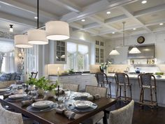 perfect play of light, combined with the warmth of wood and upholstered pieces - counting the light sources - multiple pot lights, two hanging fixtures, under cabinet downlighting, flush mounts over the window seat with flanking sconce(s), large windows and lit candles on the tabletop.
