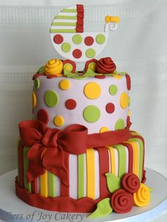 Baby shower cake with fondant dots and stripes. Fondant baby carriage and flowers.
