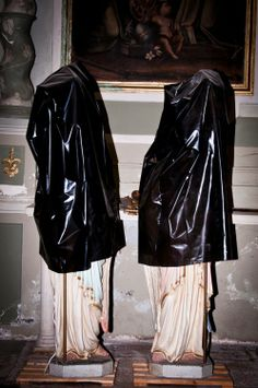 .black plastic bags over roman sculptures in a museum hall