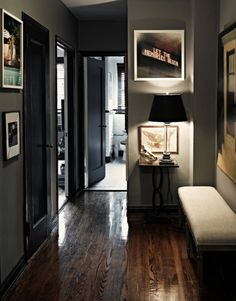 Wood floor, dark walls, and lots of pictures.