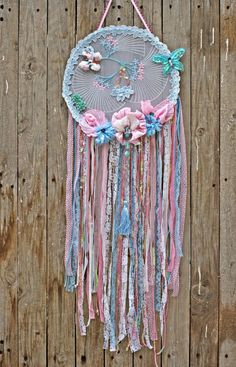 A gorgeous boho dream catcher in vintage pastel pink and blue color. An old organza fabric in ivoiry color with small embroidered pink and blue flowers, handmade flowers, costule jewelry and dangings of laces and fabric complete this hippie dreamcatcher. Perfect for any boho- hippie home decor and of course for bridal shower decor, nursery decor, boho wedding. You gonna love it !!!