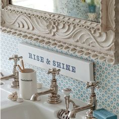 A wooden plaque stenciled with a cheerful motto and backed by pretty blue wallpaper creates a personalised country look in this period bathroom.