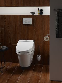 Dark, warm woods create a cozy, minimalist design complemented by a TOTO toilet. Experience TOTO high-performance toilets for yourself. #bathroomreno #bathroomgoals #interiordesign #bathroomdesign #homeinspo #minimalistdesign #toilets