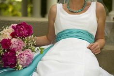 The elegant but simple wedding dress looks wonderful with the turquoise sash.
