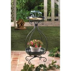 Metal Bird Feeder and Planter. This free standing bird feeder and flower pot is portable and versatile. The scrolling metal frame supports the planter base, then rises up to hold birdseed where birds can feel comfortable among your flowers.