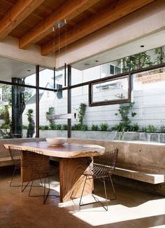 """The details that Ford credits for making the home special—""""a mixture of woods, the use of concrete, and the massive windows that bring the outside in""""—are on full display in the dining area. A beamed ceiling creates a cozy shell for the live-edge table from HD Buttercup and the concrete built-in bench. The chairs are vintage HarryBertoia."""