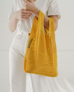 "Signature Baggu shape made from a chunky net fabric. Comes with a × expandable canvas pouch to keep your essentials secure. Mid-sized for hand carrying. 20 ½"" × 12 ½"" × 5 ½"" polyester Machine wash cold, line dry Reusable Shopping Bags, Reusable Bags, Types Of Handbags, Net Bag, Ideias Diy, Knitted Bags, Mellow Yellow, My Bags, Fashion Bags"