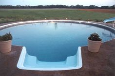 Freedom above ground pool installed completely inground with colored concrete deck, stairs, hopper bottom, and slide.
