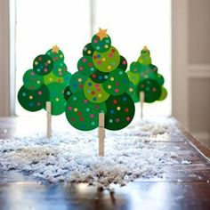"Paper Christmas Trees Craft  Using different-size circle punches, have the kids punch circles from different shades of green cardstock or scrapbook paper. Using a standard hole punch, have them make the ""ornaments"" from various bright colors of paper. Use glue stick to glue green circles together in a triangular shape (to resemble a Christmas tree). Glue small colored dots all over green circles as ornaments. Punch stars using a star punch for the tree topper; glue to the top of tree. Clip a clothespin to the bottom as the trunk."
