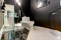 This modern powder room features an angled floor tile design and wall mirrors. Designed and built by Ramage Company.