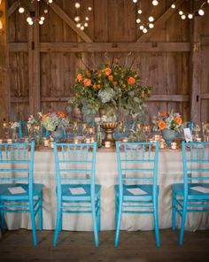 Aqua chairs are a nice contrast to the orange flowers on this wedding's reception table