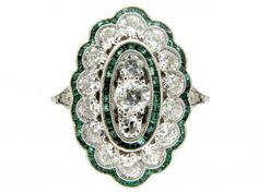 Emerald & Diamond Art Deco Ring, A very fine quality 18ct gold and platinum Art Deco ring which has been set with small shaped tramline set emeralds in a scalloped design around the edge with diamonds within that, then a further oval section with emeralds with three diamonds in the centre. Rings such as this one are rare and highly sought after.  Date & Origin	Art Deco (1920-1935)