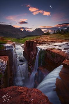 The sun and moon rise over Logan Pass, as three streams converge and fall. Glacier National Park, Montana.