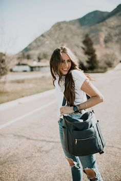 @arvowear #black #white #blue girl standing in road in white embroidered tee shirt with neck scarf and high waisted distressed denim jeans and fawn design diaper bag with long brown hair with caramel highlights loosely curled