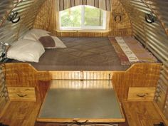 bed with a slide out table underneath for the benches. caravan trailer rv camper | ruggedthugruggedthug
