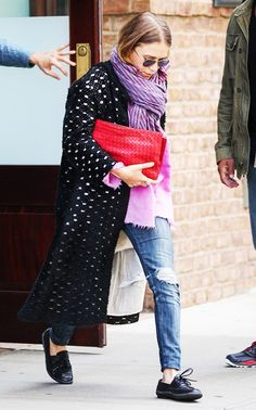 Mary-Kate Olsen wears a textured oversized outerwear, purple striped blanket scarf, ripped blue jeans and a red clutch.