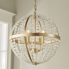 This stunningly glamorous chandelier features a globe of Soft Gold metal straps and sparkling strings of crystal for an eye-catching fixture perfect for adding a little lux to any space. 4x60 watt max candle base sockets. (21Hx18.75W). Canopy (1Hx5W). Supplied with 10 of chain and 15 of wire. OAH 142 max.