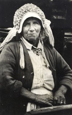 Portrait of Mrs Phil Ward, elderly boatwoman standing near a boatcabin, wearing a white bonnet and apron. Taken by Robert Longden, 1940s