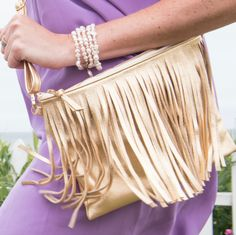 Crossbody clutch in gold leather with fringe